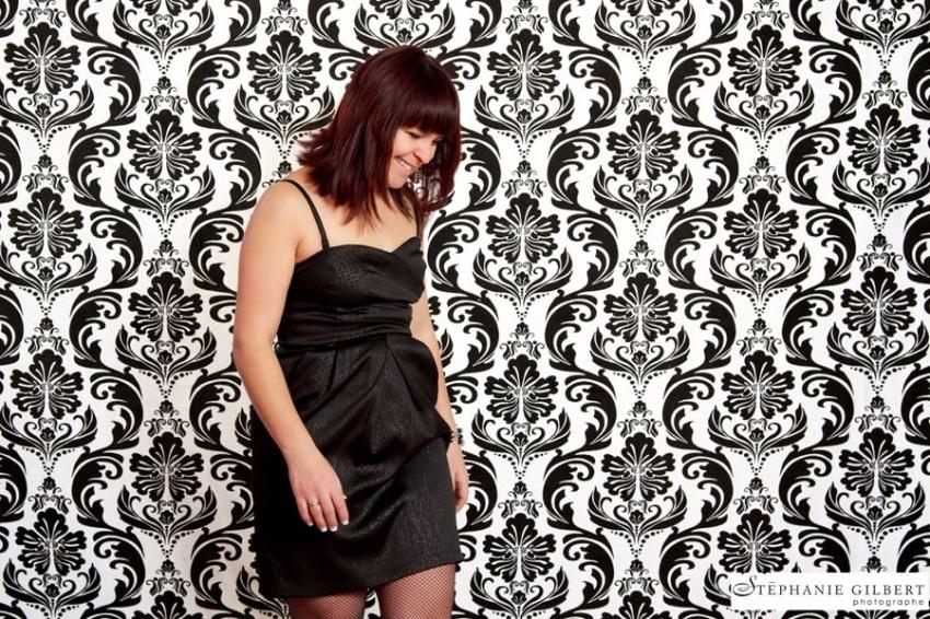 Une femme prend la pause sur un fond moderne noir et blanc.